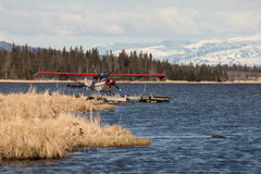 Floatplane on an Alaskan lake. Red floatplane on an Alaskan lake in fall with snow covered mountains and spruce forest in the background Stock Photos