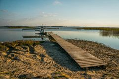 Floatplane on lake. Floatplane at wooden pier on beautiful lake Stock Photo
