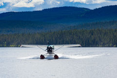 Floatplane landing remote taiga lake in Yukon T. Float plane landing on remote wilderness lake in boreal forest taiga of Yukon Territory, Canada Stock Images