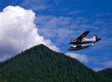 Floatplane near mountain. Floatplane coming in for landing next to mountains during approaching thunderstorm Royalty Free Stock Photo