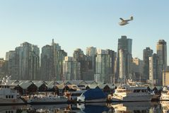 Floatplane Over Coal Harbor, Vancouver. A commuter floatplane comes in for a landing in Vancouver's Coal Harbor. British Columbia, Canada Stock Photos
