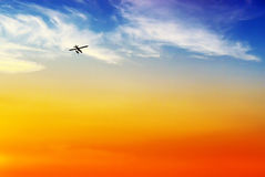 Floatplane Silhouette Flying into Sunset. The silhouette of a float or pontoon plane flies off into the sunset.  A simple minimalist background image Stock Photography