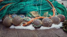 Floats and a green fishing net are piled up.  stock photo