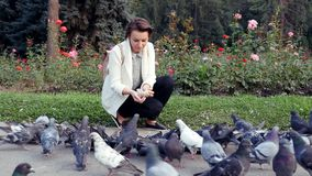 Flock of birds eating a loaf bread in park. Young girl feeds pigeons outdoors. Beautiful European girl feeds pigeons. Happy cute female woman feeding birds on stock video footage