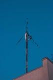 Flock of birds sitting at antenna on blue sky Stock Image