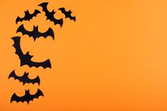 Flock of paper bats on orange wall. stock photo