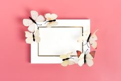 Flock of cabbage butterflies fly out from purple envelope on pink background royalty free stock image