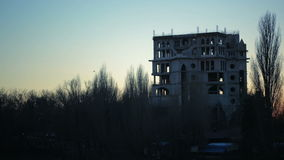 A flock of crows flying over the ruins of the building. dusk. sunset. Trees with leaves have flown stock video footage