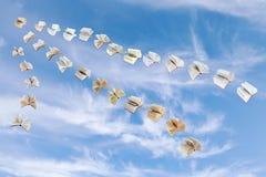 Flock of flying books in blue sky Stock Photos
