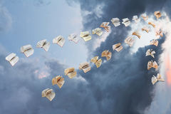 Flock of flying books in storm clouds Stock Photo