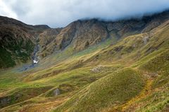 Flock of sheep grazing on green mountain slope near Sadzele pass, Georgia royalty free stock photography