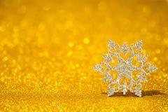 Floco de neve de brilho em um fundo brilhante dourado Brilho do brilho com forma 3d Fotografia de Stock