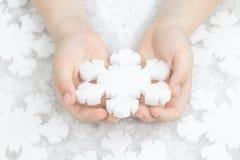 Floco de neve de cristal do Natal da terra arrendada da criança no branco imagem de stock