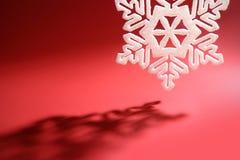 Floco de neve de encontro ao vermelho imagem de stock