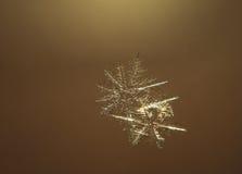Floco de neve próximo acima no ar no fundo amarelo brilhante fotos de stock royalty free
