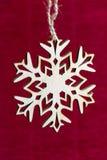 Floco de neve que pendura em uma corda em um fundo vermelho, ano novo, Chris Fotos de Stock