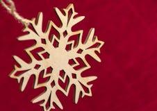 Floco de neve que pendura em uma corda, fundo vermelho, ano novo, Natal Imagem de Stock
