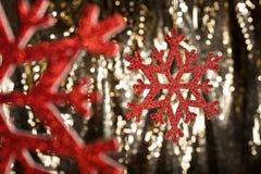 Floco vermelho da neve em um fundo do glitter do ouro Fotos de Stock Royalty Free