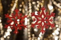 Floco vermelho da neve em um fundo do glitter do ouro Imagens de Stock Royalty Free