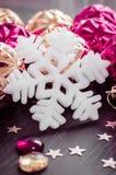 Flocon de neige blanc sur le fond des babioles de Noël de magenta et d'or images stock