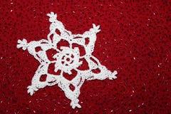 Flocon de neige de dentelle de crochet avec le fond perlé rouge Photographie stock