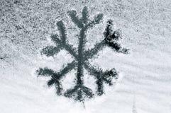 Flocon de neige dessiné dans la neige Photographie stock