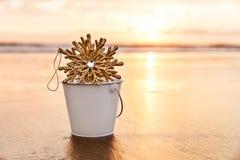 Flocon de neige de Noël dans un coucher du soleil blanc de l'AR de seau sur la plage dedans Photo libre de droits