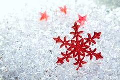 Flocon de neige rouge de Noël sur la glace de l'hiver Image libre de droits