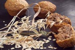 Flocons d'avoine, grains et gâteaux faits maison sur un fond foncé image stock