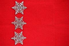 Flocons de neige argentés sur le fond rouge Photographie stock