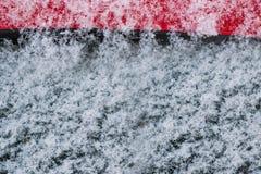 Flocons de neige blancs, neige sur le verre noir et métal rouge, abstrait Image libre de droits