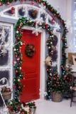 Flocons de neige décoratifs à l'arrière-plan au tuyau avec la porte rouge Photographie stock libre de droits