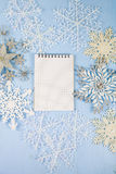 Flocons de neige décoratifs argentés et un carnet sur un CCB en bois bleu Images libres de droits