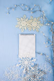 Flocons de neige décoratifs argentés et un carnet sur un CCB en bois bleu Image stock