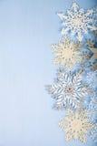 Flocons de neige décoratifs argentés sur un fond en bois bleu christ Images libres de droits