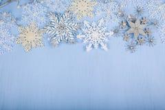 Flocons de neige décoratifs argentés sur un fond en bois bleu christ Photo stock