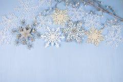 Flocons de neige décoratifs argentés sur un fond en bois bleu christ Photographie stock