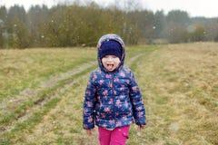 Flocons de neige de capture mignons de petite fille premiers avec sa langue le jour d'automne Image stock