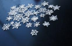 Flocons de neige de livre blanc sur le fond bleu-foncé Image stock