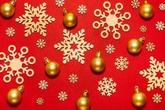 Flocons de neige en bois et boules de nouvelle année d'or sur un fond rouge Photos libres de droits