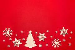 Flocons de neige et arbre de Noël en bois sur le fond rouge Image stock