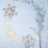 Flocons de neige et branche décoratifs argentés sur un backgro en bois bleu Photographie stock