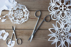 Flocons de neige et ciseaux de papier fait main Photographie stock