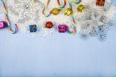 Flocons de neige et neige décoratifs argentés sur un backgroun en bois bleu Photographie stock libre de droits