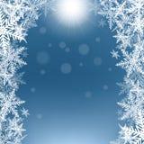 Flocons de neige et soleil de Noël sur le fond bleu Photographie stock libre de droits