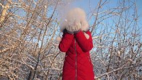 Flocons de neige de soufflement de fille heureuse au coucher du soleil et sourire en parc d'hiver la jeune fille souffle des floc banque de vidéos