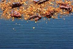 Flocons des poivrons de piment d'un rouge ardent sur le fond en bois Photos stock