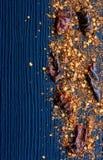 Flocons des poivrons de piment d'un rouge ardent sur le fond en bois Photographie stock libre de droits