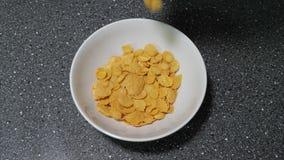Flocos de milho de derramamento na bacia branca na tabela cinzenta que prepara o café da manhã filme