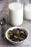 Flocos de milho dourados e do chocolate em uma bacia e em um vidro do leite na tabela de madeira Fotografia de Stock Royalty Free